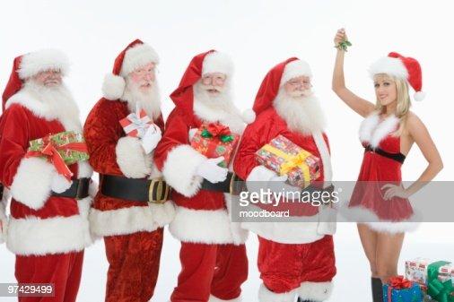 Group Of Men Dressed As Santa Claus Mrs Claus Holding Mistletoe Stock Photo