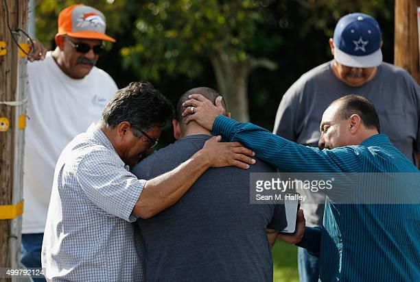 A group of men embrace in prayer outside the crime scene where the suspects in the shooting at the Inland Resource Center were killed on December 3...