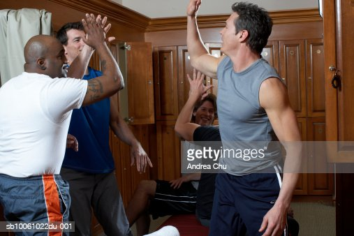 Group of men exchanging high-fives in locker room : Stock Photo