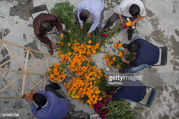 A group of men gather to make a floral arrangement for their dead in Janitzio on October 31 2015