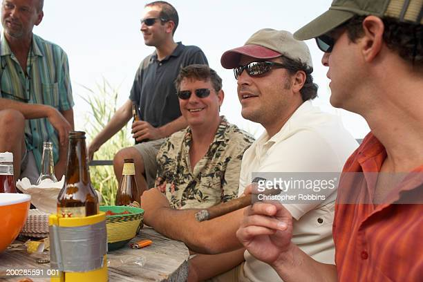 Group of men having drinks around table outdoors, smiling