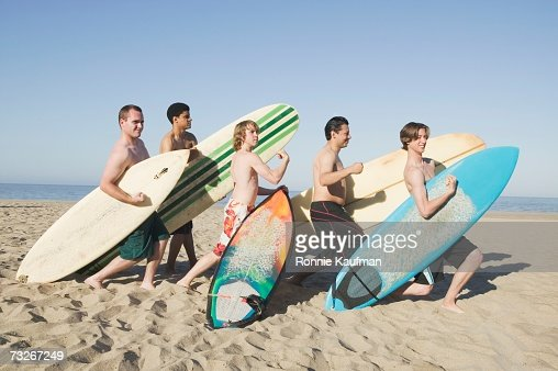 Group of men holding surfboards and flexing on beach : 스톡 사진