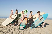 Group of men holding surfboards and flexing on beach