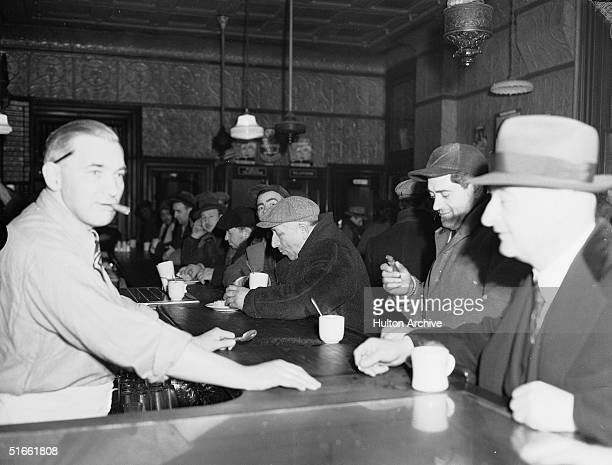 A group of men in coats and caps eat and drink as they sit at the bar in an establishment frequented by fisherman in the Fulton Fish Market area of...