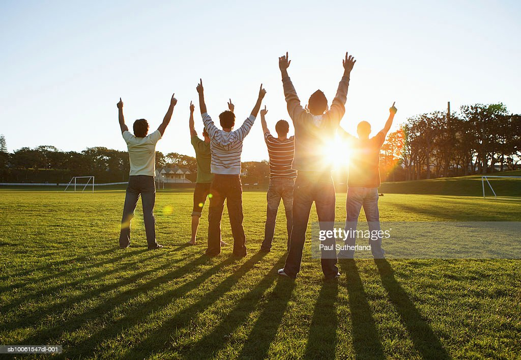 Group of men in park, outstretching arms against sun, rear view : Stock Photo