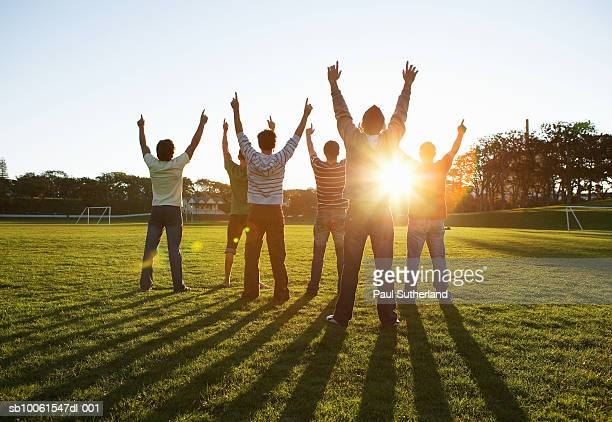 Group of men in park, outstretching arms against sun, rear view