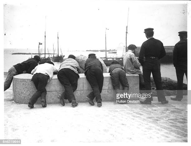 A group of men lean over a low wall overlooking Barfleur harbor