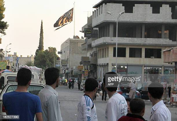 A group of men look at a large black Jihadist flag with Islamic writing on it proclaiming in Arabic that 'There is no God but God and Mohammed is the...