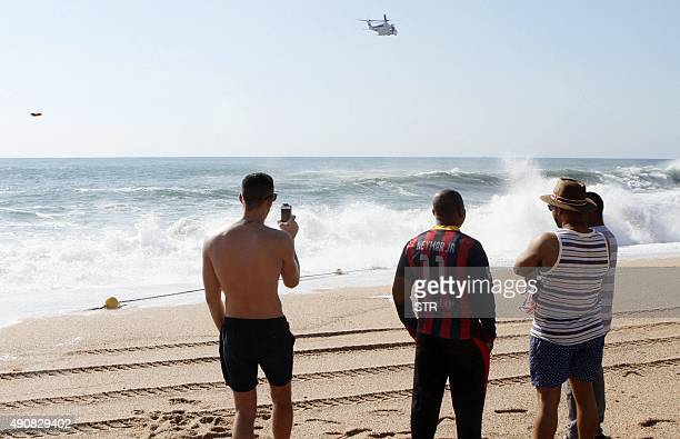 A group of men look at a rescue helicopter overflying the beach of Lloret de Mar northeastern Spain where the drowned bodies of two British women...
