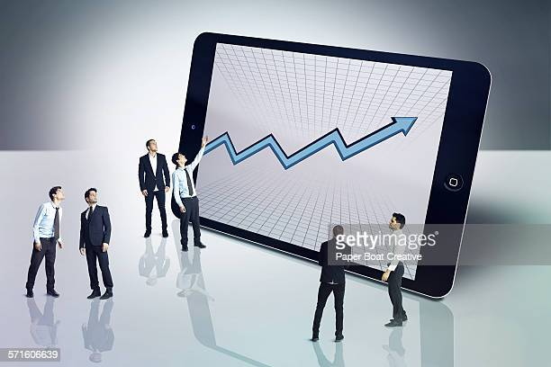 Group of men looking at charts on a digital tablet