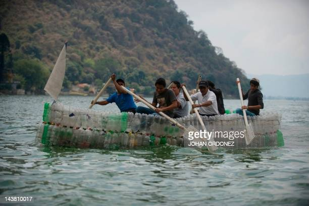 A group of men paddle aboard a boat made out of recycled plastic bottles in the Amatitlan Lake Amatitlan municipality 35 km south of Guatemala City...