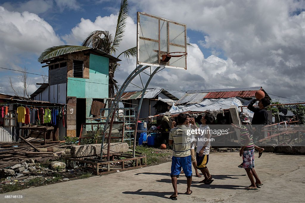 A group of men play basketball on April 19, 2014 in Tacloban, Leyte, Philippines. Basketball is the most popular sport in the Philippines. In the aftermath of Superstorm Yolanda that struck the coast on November 8, 2013 leaving more than 6000 dead and many more homeless, basketball hoops were some of the first things to be repaired and rebuilt amongst the rubble, showing the Filipino's resilience and intense love for the sport. Five months after the storm, basketball courts have re-emerged in large numbers across the damaged provinces using any available space and many being rebuilt from storm debris.
