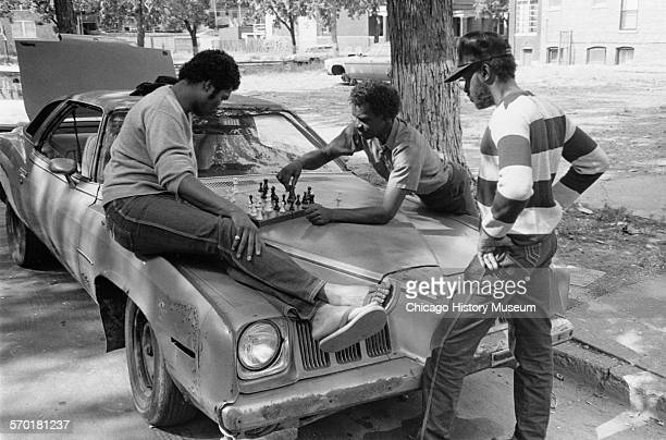 Group of men playing a chess game on car hood at 62nd Street between Langley Avenue and Champlain Avenue Chicago Illinois September 27 1987