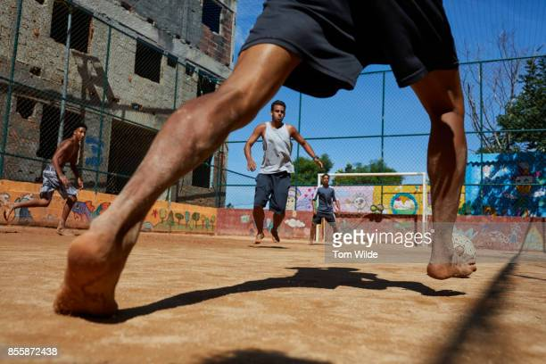 Group of men playing football on a dirt court in Rio de Janeiro