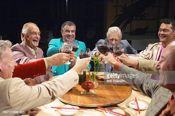Group of men raising glasses in restaurant