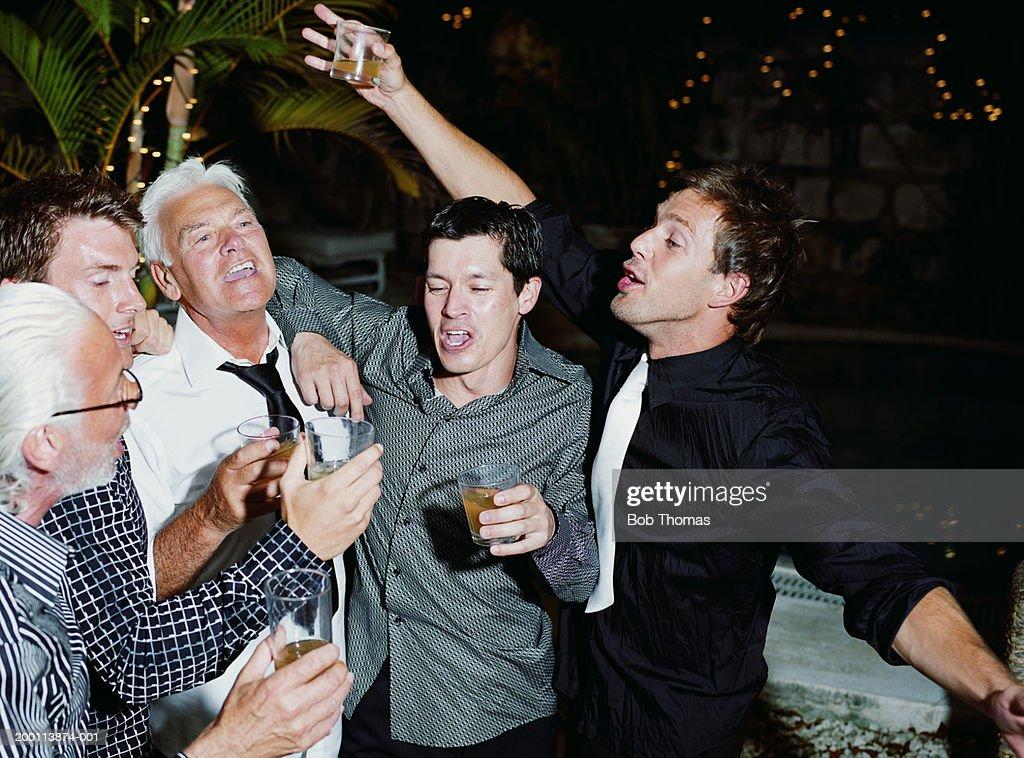 Group of men raising toast outdoors, night