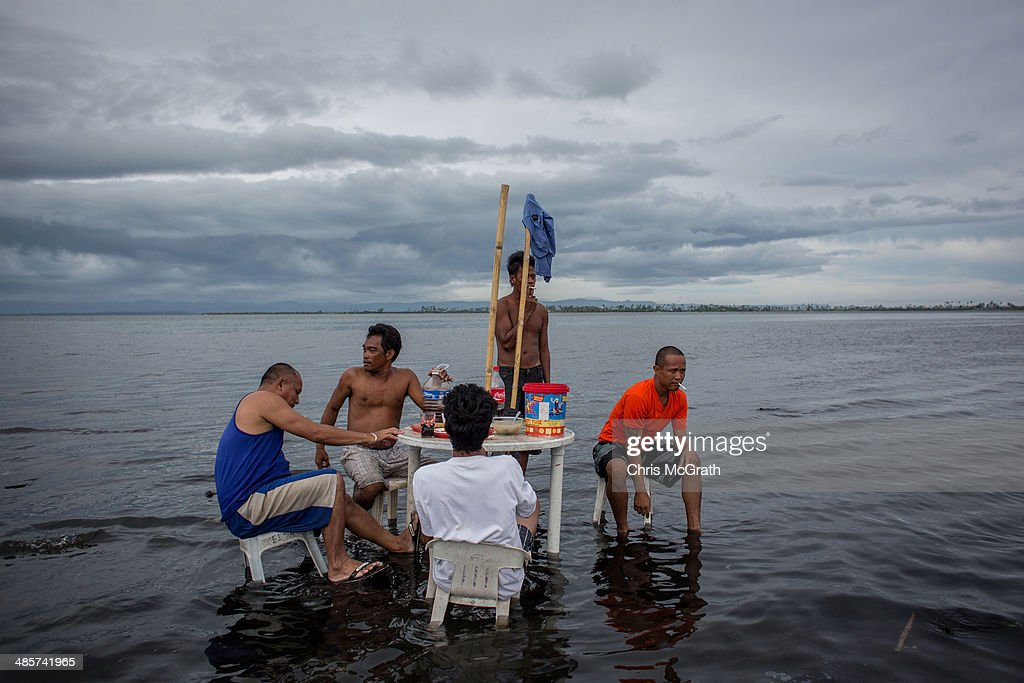 A group of men relax and drink Tuba (coconut wine) on a table off the beach on April 20, 2014 in Tacloban, Leyte, Philippines. People continue to rebuild their lives five months after Typhoon Haiyan struck the coast on November 8, 2013, leaving more than 6000 dead and many more homeless. Although many businesses and services are functioning, electricity and housing continue to be the main issues, with many residents still living in temporary housing conditions due to 'No Build' areas preventing them from rebuilding their homes. This week marks Holy Week across the Philippines and will see many people attending religious activities.