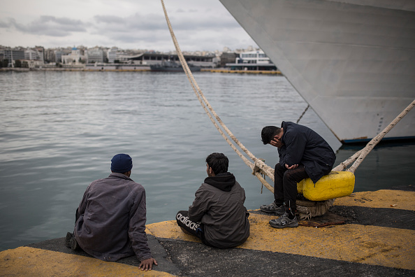 A group of men sits facing the sea outside a passenger terminal used as shelter for refugees and migrants at the Piraeus harbour in Athens on March 12, 2016