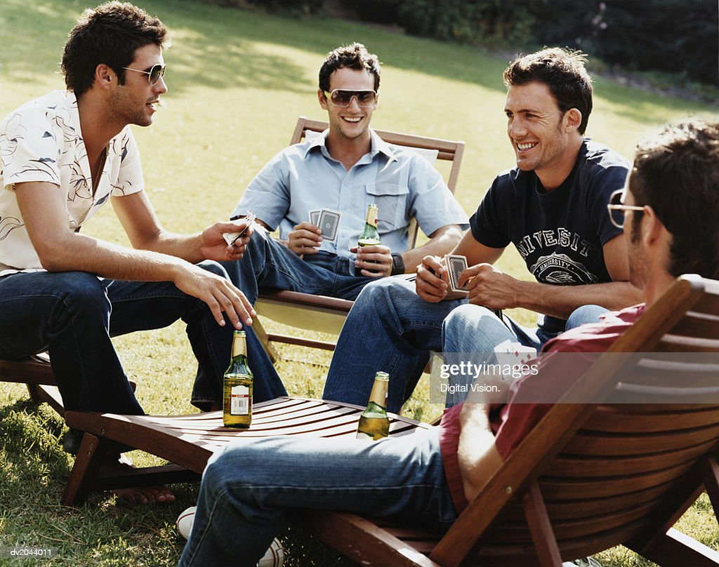 Group of Men Sitting on Sunloungers Playing Cards and Drinking Beer : Stock Photo