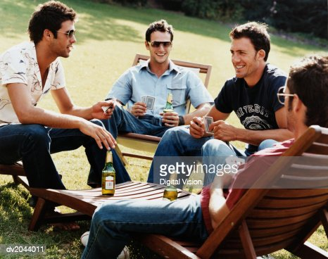 Group of Men Sitting on Sunloungers Playing Cards and Drinking Beer : ストックフォト