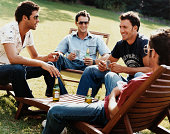 Group of Men Sitting on Sunloungers Playing Cards and Drinking Beer