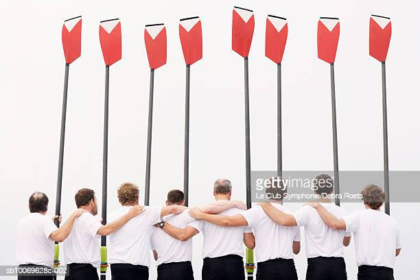 Group of men standing in row holding oars in air, rear view