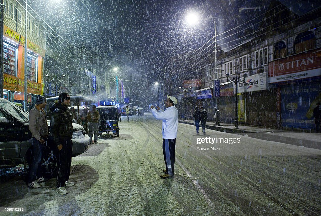 A group of men take pictures during heavy snowfall on January 17, 2013 in Srinagar, Indian Administered Kashmir, India. Several parts of the Kashmir Valley, including the summer capital Srinagar, experienced fresh snowfall today, prompting the authorities to issue an avalanche warning and leading to closure of the Jammu-Srinagar Highway, the only road link between Kashmir and rest of India.