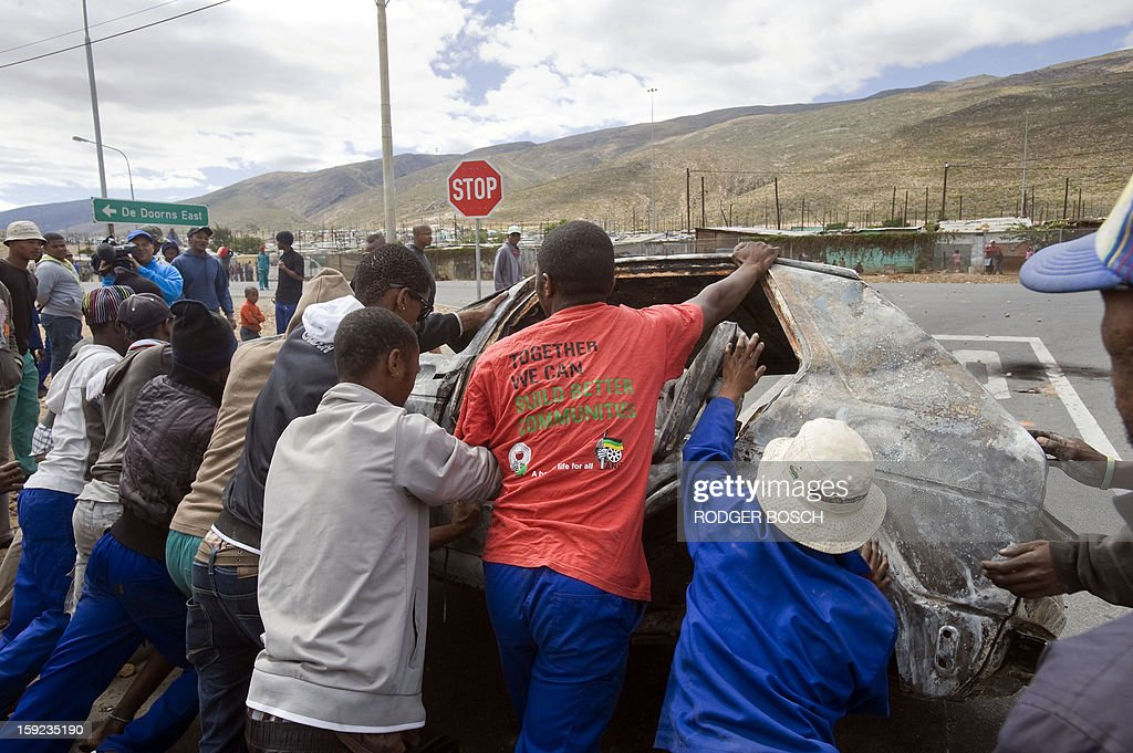 A group of men try to roll a burnt out car onto the N1 highway, in ongoing violence during the farmworkers strike, on January 10, 2013 in de Doorns, a small farming town about 140Km North of Cape Town, South Africa. The farm workers have said that they they will not return to work on the fruit growing region's farms until they receive a daily wage of at least R150($17) per day, which is about double what they currently earn. One of the men wears a red t-shirt of the ruling African National Congress(ANC).