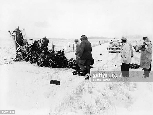 A group of men view of the wreckage of a Beechcraft Bonanza airplane in a snowy field outside of Clear Lake Iowa early February 1959 The crash on...
