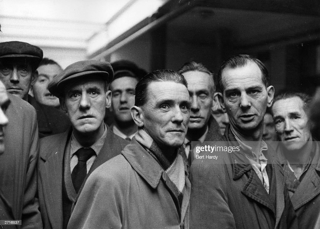 A group of men wait hopefully at a Labour Exchange in Derry where unemployment affects one man in five. Original Publication: Picture Post - 8199 - One Man In Five Is Out Of Work - pub. 1955