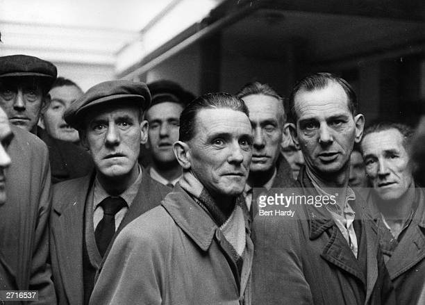 A group of men wait hopefully at a Labour Exchange in Derry where unemployment affects one man in five Original Publication Picture Post 8199 One Man...