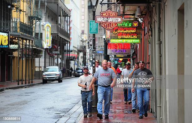 A group of men walk along a deserted Bourbon Street in New Orleans on August 28 2012 in Louisiana where Hurricane Isaac has made landfall The US...