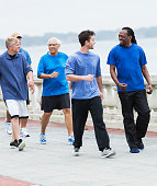 Multi-ethnic group of men wearing casual workout clothing, walking on a pedestrian walkway, talking.  All are wearing blue shirts.
