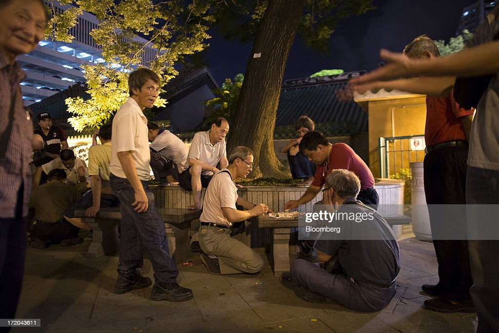 A group of men watch a game of Chinese chess in a park in the Yau Ma Tei district of Hong Kong, China, on Saturday, June 29, 2013. Hong Kongs best-selling newspapers called on readers to join a march to mark the anniversary of the citys handover to China, saying the government has failed to address issues of poverty and universal suffrage. Photographer: Jerome Favre/Bloomberg via Getty Images