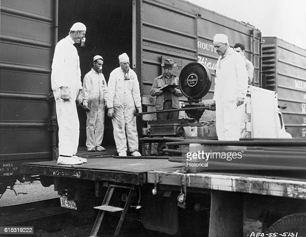 A group of men watch as one weighs uranium bars unloaded from a railroad car in Hanford Washington Ca 19471972