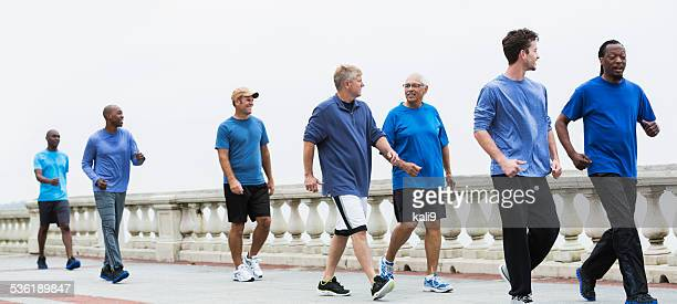 Group of men wearing blue shirts, power walking