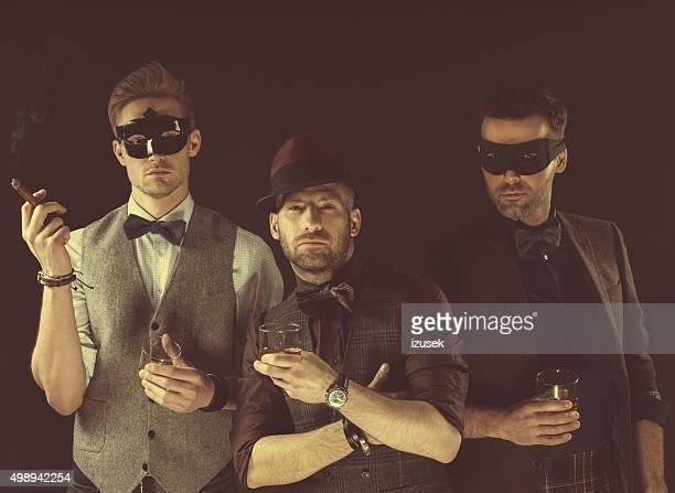 Group of men wearing carnival masks, holding drinks