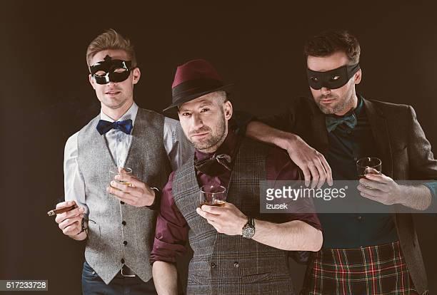 Group of men wearing carnival masks, holding whiskey