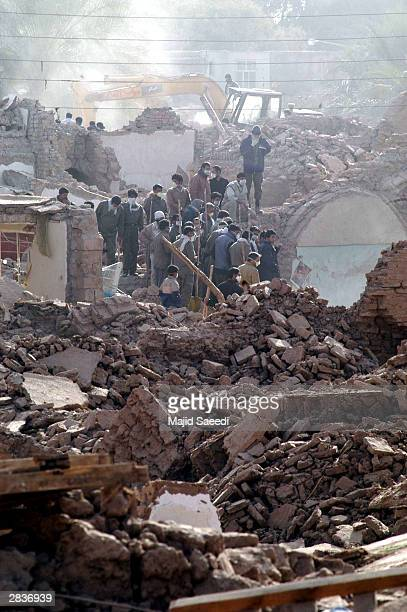 A group of men work to clear rubble and debris left by an earthquake December 30 2003 in Bam Iran The quake registering approximately 65 on the...