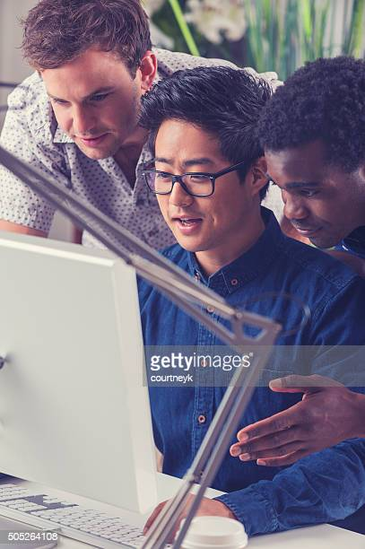 Group of men working on creative ideas with a computer.