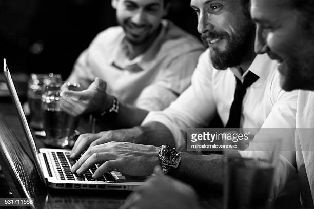 Group of men working on laptop in a pub