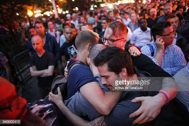 A group of mens embraces each other as they part during a vigil in solidarity outside Manhattan's historic Stonewall Inn to express their support for...