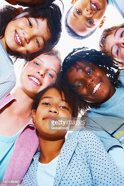 Group of middle school children looking down and smiling