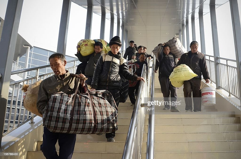 A group of migrant workers carry bags as they walk down a flight of stairs at a bus station in Beijing on November 21, 2012. China's Communist leaders are promising to revolutionise the world's second largest economy and move on from being the world's workshop, but economists say the monumental task faces major hurdles.