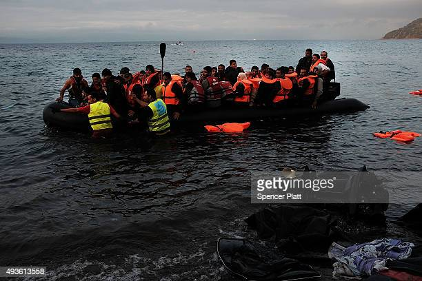 A group of migrants arrives onto the beach from Turkey on the island of Lesbos on October 21 2015 in Sikaminias Greece Dozens of rafts and boats are...