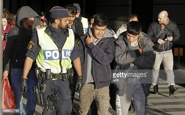A group of migrants off an incoming train walk down a platform as they are accompanied by the police at the Swedish end of the bridge between Sweden...