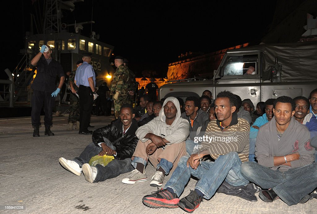 A group of migrants rest shortly after they were rescued and brought ashore to the Armed Forces of Malta Maritime base, on November 9, 2012 in Valletta. The Maltese military rescued 250 undocumented migrants believed to be Eritrean from a stricken boat, officials said, after reports the vessel had been adrift for days. AFP PHOTO/Matthew Mirabelli -MALTA