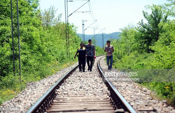 A group of migrants walk on a railroad tracks a few kilometers from the MacedonianGreek border in Gevgelijain southern Macedonia on May 5 as migrants...
