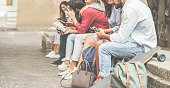 Group of millennials friends using smartphones  outdoor - Happy people having fun with technology trends after university lesson - Youth and friendship concept - Focus on right man mobile phone