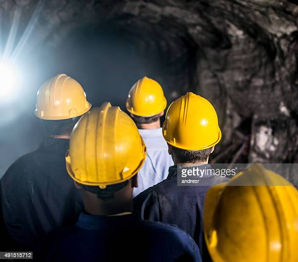 Group of miners walking into a mine